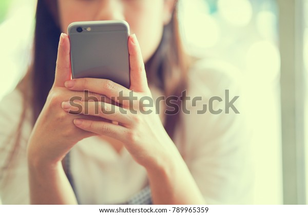 close up businesswoman hand holding smartphone for checking information from email or playing social media application in free time , technology concept
