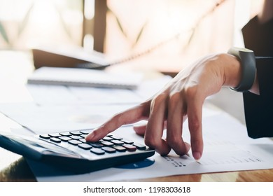 Close up of businesswoman. Hands holding phone and calculator on office working table