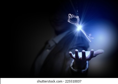 Close up of businesswoman holding golden key in hand