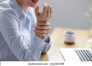 Close up businesswoman holding hand feeling wrist pain from using laptop long time. Young employee suffering carpal tunnel syndrome from intensely using mouse and typing on keyboard. Computer overwork