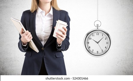 Close up of a businesswoman holding a paper cup of coffee and a notebooks and standing near a concrete wall with giant stopwatch