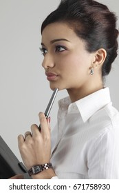 Close up of businesswoman holding pen and notebook