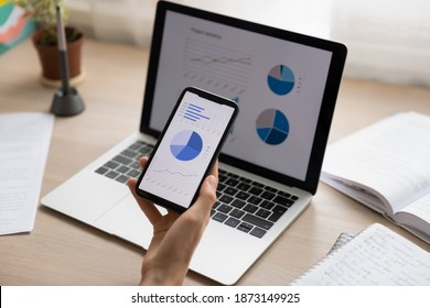 Close up businesswoman holding working with project statistics on devices, presentation with graphs and diagrams on laptop and phone screens, entrepreneur accountant analyzing financial data