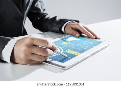 Close of businesswoman sitting at table and touching with stylus tablet pc screen