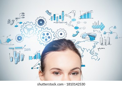 Close up of businesswoman standing near concrete wall with gears sketch drawn on it. Elements of this image furnished by NASA