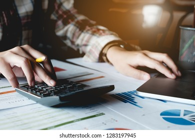 Close up Businesswoman using calculato for do math finance on wooden desk in office and business working background, tax, accounting, statistics and analytic research concept