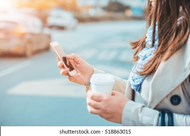 Close up of businesswoman using smart phone.Young business woman enjoying coffee break.