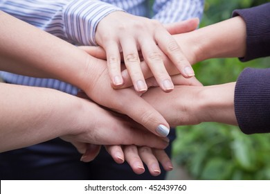 Close up of businesswomen holding hands in unity and supporting each other. Team building.