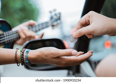 close up of busker hand receiving coin given by someone from the car on the road