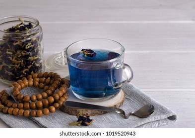 Close up of Butterfly pea flower tea cup and mala beads,  dried flower of Clitoria Clitoria ternatea plant on the back. Asian exotic blue tea background with copy space