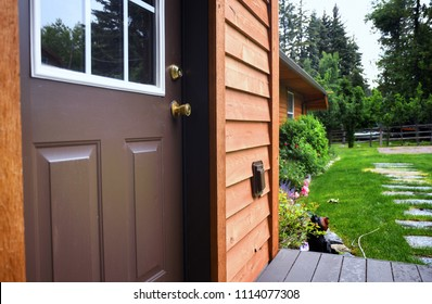 Close up of a cabin door with a garden behind it