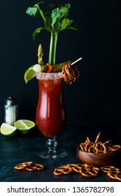 A close up of a Caesar cocktail otherwise known as a Bloody Mary garnished with celery, pickles, pretzels and a lime ready for drinking.