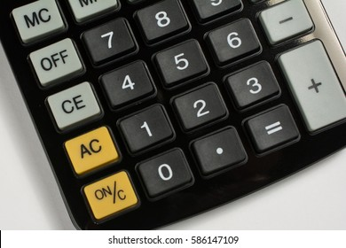 Close up of a calculator angled to the side on white.