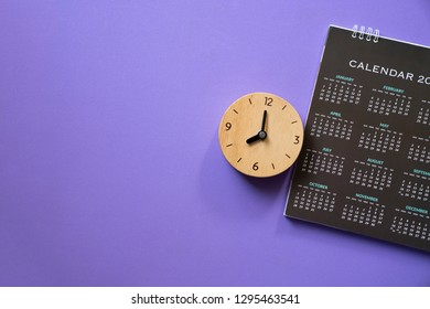 close up of calendar and alarm clock on the purple table background, planning for business meeting or travel planning concept