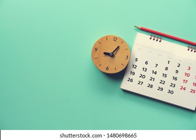 close up of calendar and alarm clock on the green table, planning for business meeting or travel planning concept