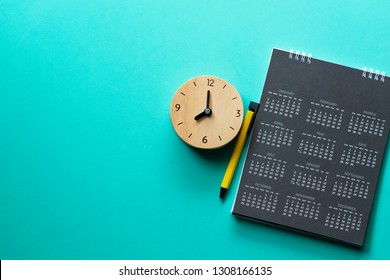 close up of calendar, clock and on the green background, planning for business meeting or travel planning concept