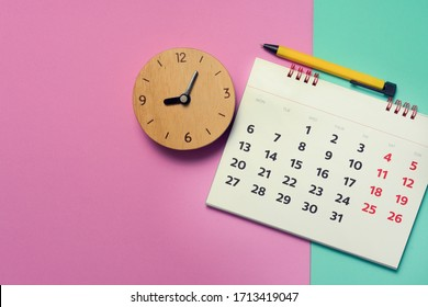 close up of calendar and clock on the pink and green table, planning for business meeting or travel planning concept