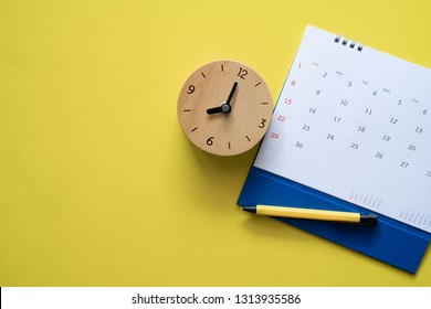 close up of calendar, clock and pen on the yellow table, planning for business meeting or travel planning concept