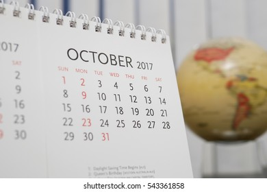 Close up calendar of October 2017 with blur earth globe background
