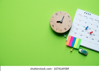 close up of calendar on the table with clock and green background, planning for business meeting or travel planning concept