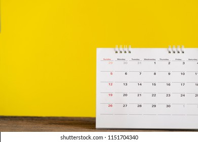 close up of calendar on the table with yellow background, planning for business meeting or travel planning concept