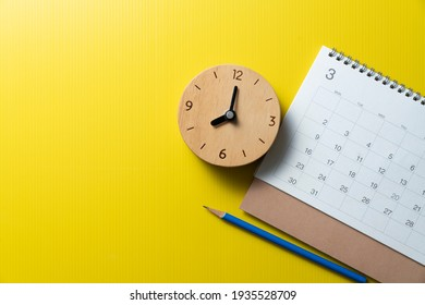 close up of calendar, pencil, alarm clock on the yellow table background, planning for business meeting or travel planning concept