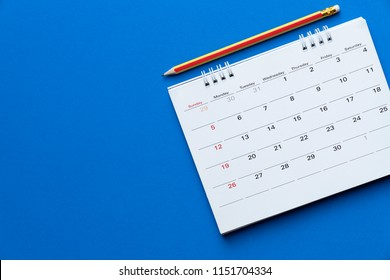 close up of calendar and pencil on the blue background, planning for business meeting or travel planning concept