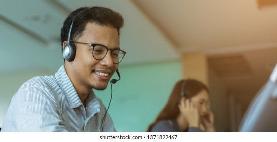 close up call center latin manwear headset for talking with customer and working with asian employee colleague woman at operation room , help desk support concept