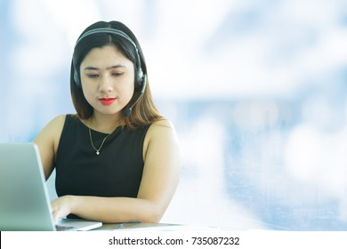 close up call centre asian girl working and response answer to customer or partner over blurred building city background,isolated with paths