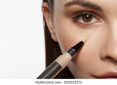 Close up of calm girl applying foundation under eye area by special brush. Macro concept. Isolated and copy space