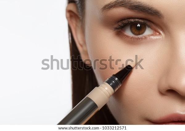 特殊なブラシで目の下の基礎を塗る穏やかな少女の接写。マクロのコンセプト。分離/コピー用スペース