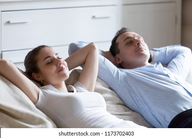 Close up of calm man and woman lying on cozy couch hands over head relaxing after working day, peaceful husband and wife rest on sofa with eyes closed taking nap, tired parents chill in living room