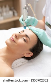 Close up of calm relaxed lady lying with her eyes closed and professional cosmetologist cleaning her skin with dermabrasion tool