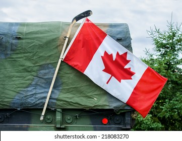 A close up of a Canadian flag attached to a hockey stick hanging on the side of a Canadian Armed Forces military personnel transport truck demonstrating national pride.