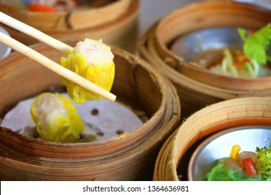 Close up Cantonese Shumai (Siu Mai) Dim Sum, shrimp & pork Chinese steamed dumplings wrap by yellow wonton wrapper (Kanom Jeeb in Thai) in bamboo basket in dim sum set
