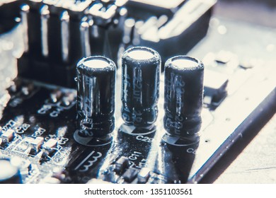 Close up of capacitors installed on a black motherboard to store charges and release energy when needed by the logic board