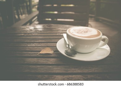 Close up of cappuccino coffee with a cup on the wood table. Selective focus and vintage color tone.