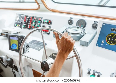 Close up captain hand on boat steering wheel
