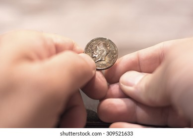 Close up capture of an Caucasian man hands holding and old greek new years cake coin showing king face