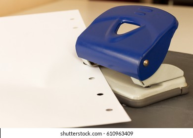 Close up capture of navy blue hole puncher, white paper on grey ground at office