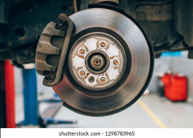 Close up of car disc brake during the wheel tire change or repair. Disc brake of the car during the maintenance at auto service garage.