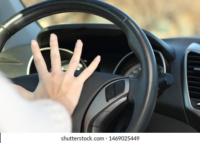 Close up of a car driver hand honking horn