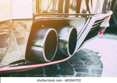 Close up of a car dual exhaust pipe in sunlight background
