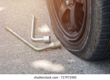 Close up Car flat tire on the road with repair tools, sun light filter