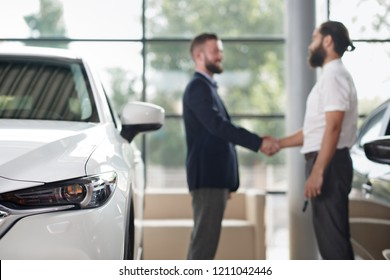 Close up of car headlight. Men standing, shaking hands, making deal on background. Customer wearing in white shirt, manager in dark blue jacket. Businessman purchasing white automobile in car center.