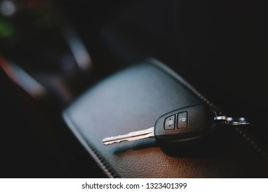 Close up of a car key ring and remote control alarm system charm in vehicle new car interior. soft focus.