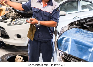 Close up of a car mechanic checking engine oil level at car repair center shop.