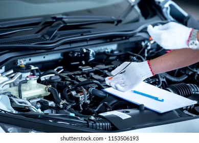 Close up of a car mechanic checking oil level in a mechanical workshop