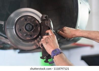 Close up of car mechanic repairing brake pads