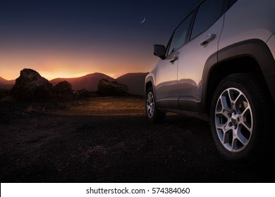 Close up of a car on a desert road at the sunset with copy space